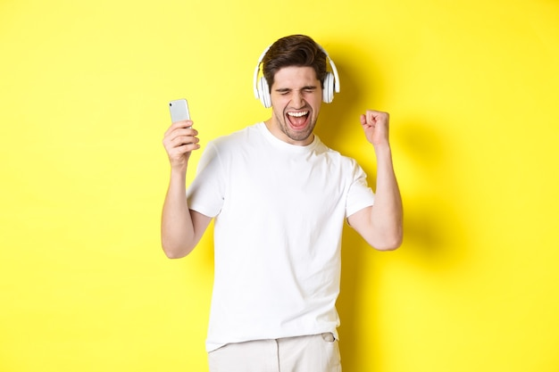 Happy man dancing and listening music in headphones, holding mobile cell phone, standing against yellow background