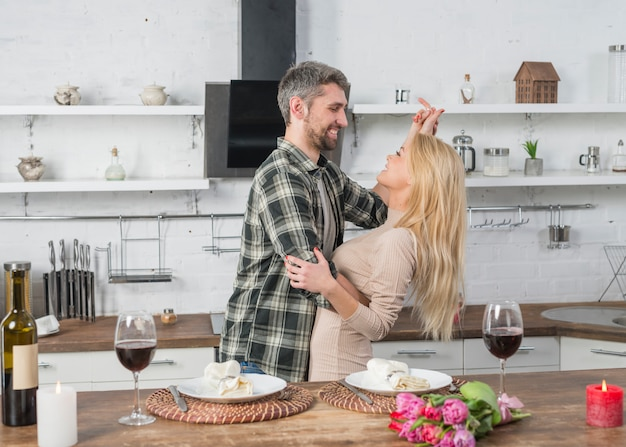 Happy man dancing with blond woman near table in kitchen