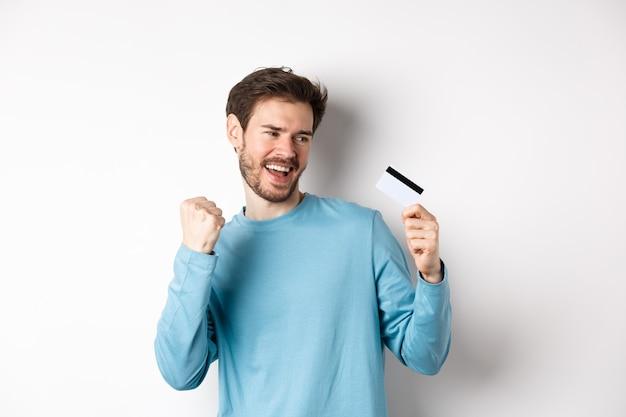 Счастливый человек танцует с пластиковой кредитной картой, улыбаясь и говоря «да», празднуя на белом фоне. копировать пространство