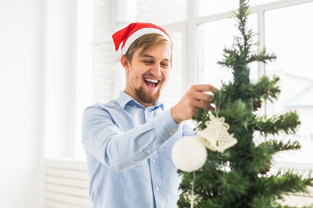 Happy man decorating christmas tree at home with santa claus hat. man decorating tree with baubles