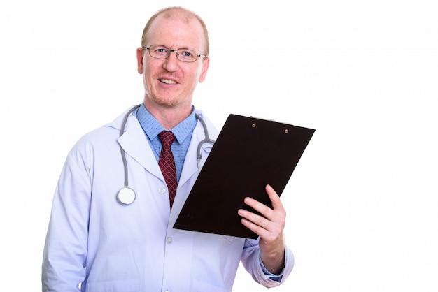白で隔離されるクリップボードを押しながら笑って幸せな男医師