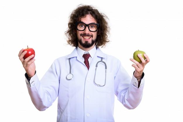 赤いリンゴと青リンゴを押しながら笑って幸せな男医師