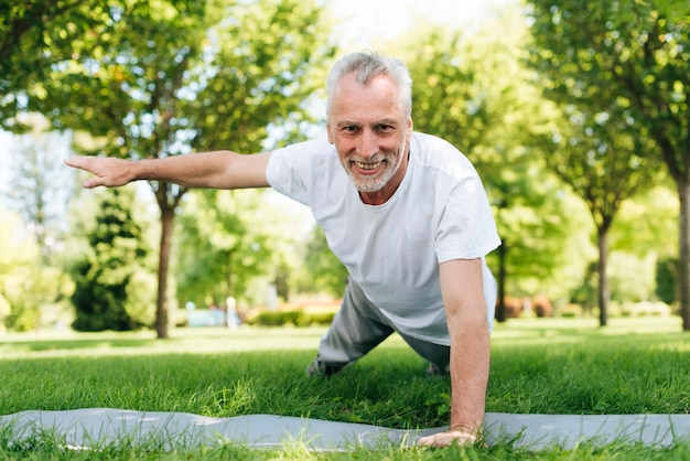 Happy man doing push-ups in nature