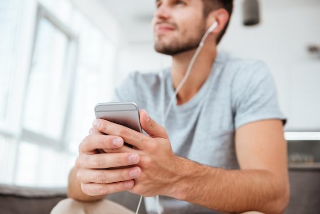 소파에 앉아 옆으로 보는 동안 음악을 듣고 티셔츠를 입은 행복한 사람. 핸드폰과 손에 중점을 둡니다.