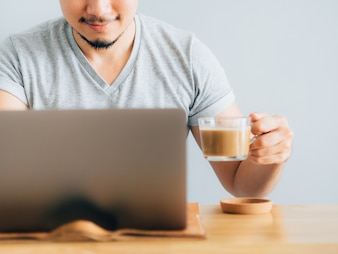 Happy man drink coffee while use laptop.
