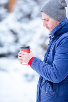 Happy man drinking coffee outdoors in winter time