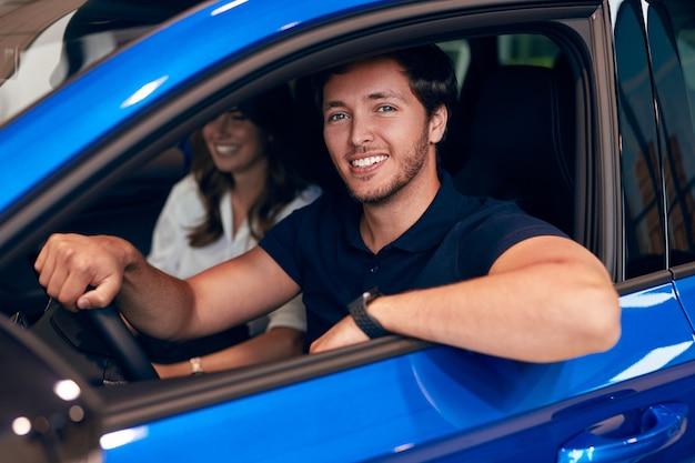 ディーラーで車を運転する幸せな男