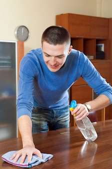 Happy man dusting  table with rag and cleanser at home