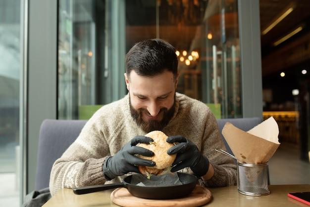 レストランでハンバーガーを食べて幸せな男