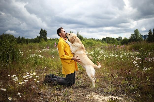 森の牧草地で犬を抱きしめる幸せな男