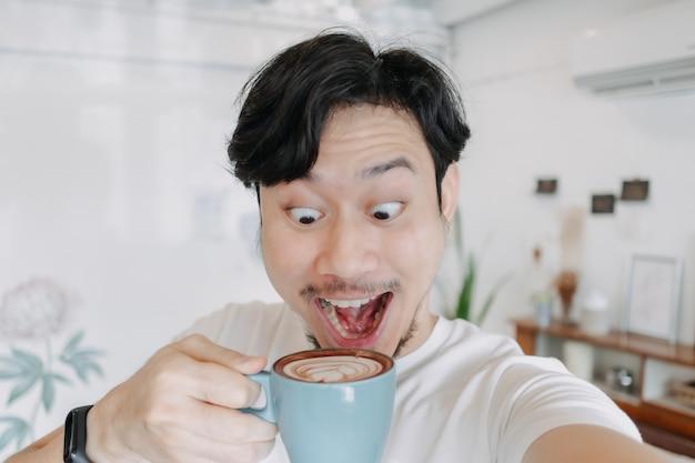 幸せな男は彼のコーヒーカップで彼のコーヒーと自分撮りを楽しんでいます