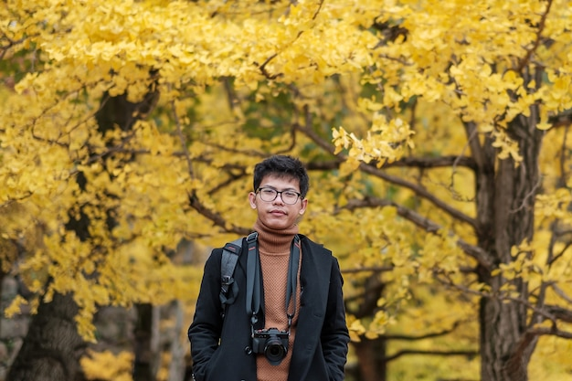 Happy man enjoy at the park outdoor in autumn season, asian traveler in coat and camera against yellow ginkgo leaves background