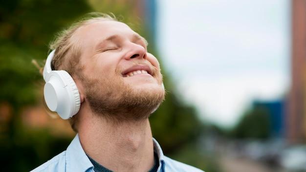 ヘッドフォンで音楽を楽しんで幸せな男
