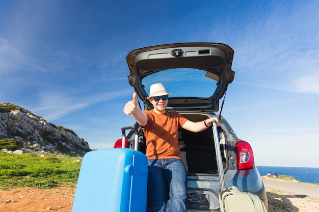 Happy man enjoying road trip and summer vacation. travel, holidays and people concept