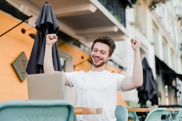 Счастливый человек рад своей победе на ноутбуке