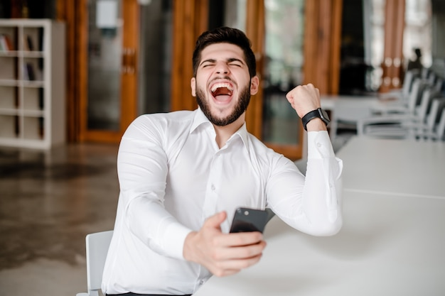 Happy man excited about win on his phone in the office