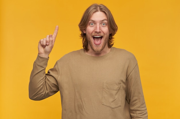 행복한 사람, 금발 헤어 스타일, 수염 및 콧수염을 가진 흥분된 남자. 베이지 색 스웨터를 입고. 손가락을 들어 올려 넓게 웃습니다. 아이디어가 있습니다. 노란색 벽 위에 절연