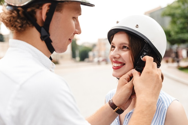 Happy man fastens a helmet to his girlfriend outdoors