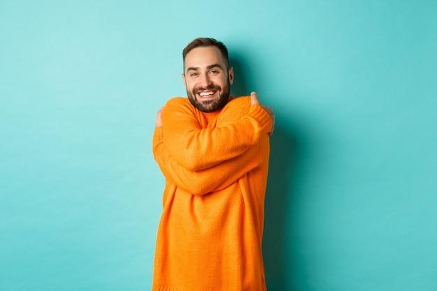 幸せな男は快適に感じ、暖かいセーターを着て抱きしめ、満足のいく笑顔で、明るいターコイズブルーの壁の上に立っています。