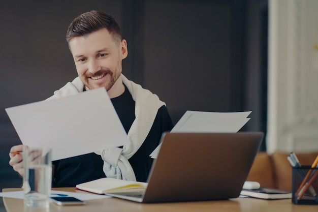 Happy man freelancer or businessman in casual wear sitting at table, looking at project report with satisfied face expression. male manager doing paperwork while at comfortable workplace with laptop