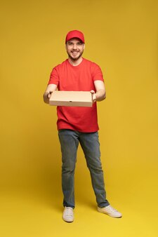 Happy man from delivery service in red t-shirt and cap giving food order and holding pizza box isolated over yellow wall