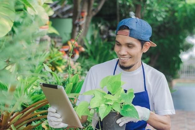 행복한 남자 정원 가게 주인은 인터넷 상점에서 태블릿 판매 온라인 작은 꽃을 사용합니다.