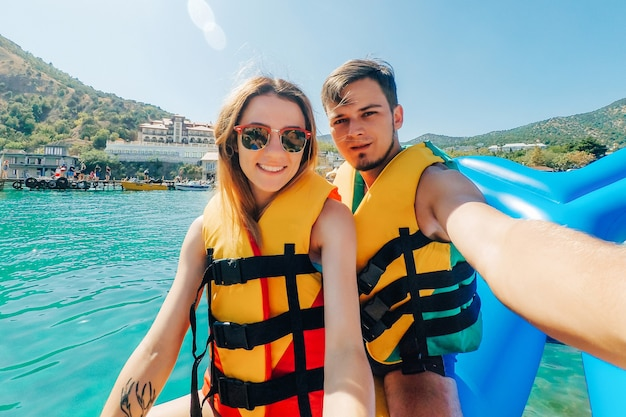Happy man and girl take a selfie riding on the sea on a banana boat