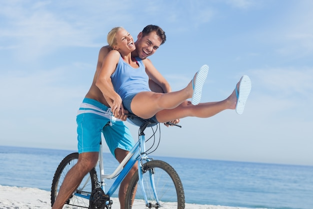 Happy man giving girlfriend a lift on his crossbar