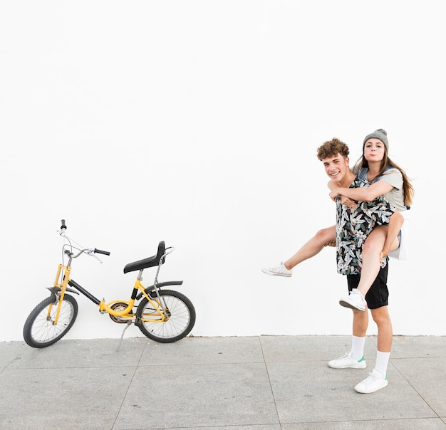 Happy man giving piggyback to his girlfriend near yellow bicycle on sidewalk