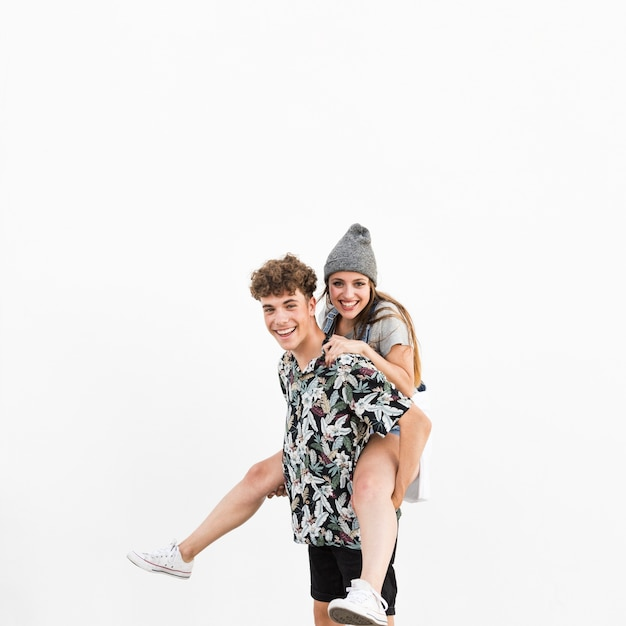 Happy man giving piggyback to his girlfriend on white background