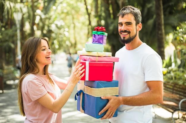 彼のガールフレンドに贈り物のスタックを与える幸せな男