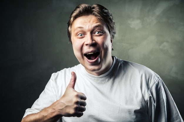Happy man giving thumbs up sign on gray background