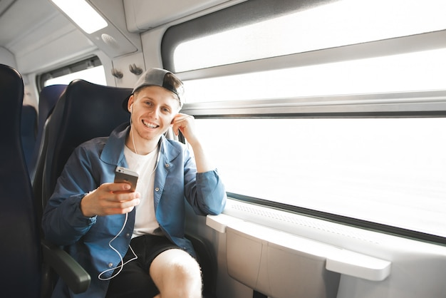 Happy man goes on a train, listens to music in the headphones, holds the phone in his hands