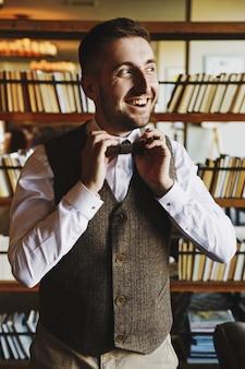 Happy man in grey waistcoat poses in the dark library