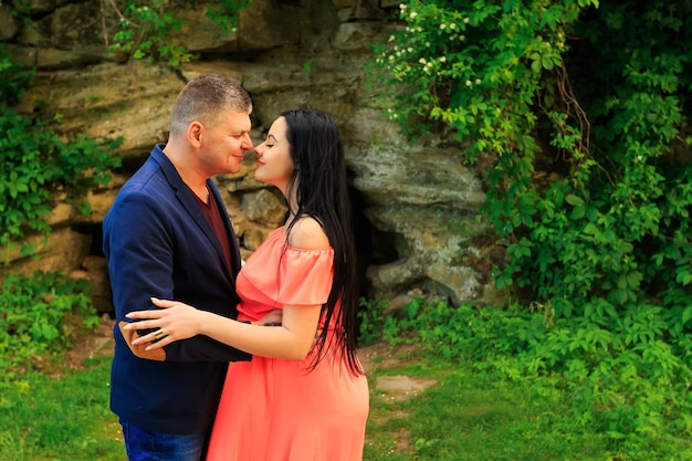 Happy man and his pregnant woman in pink dress outdoors near the rocks and greenery