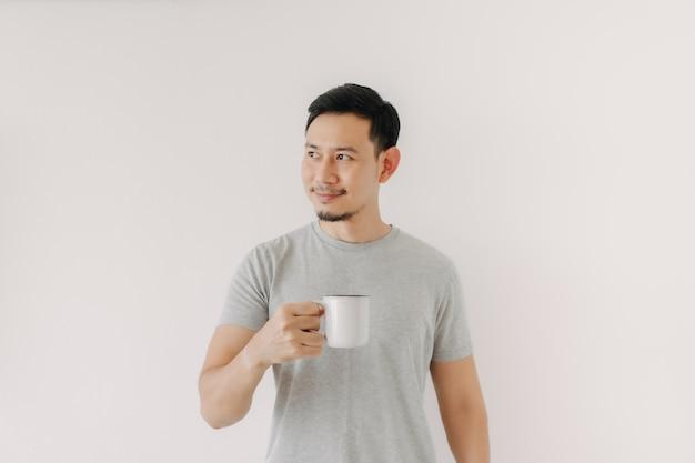 幸せな男は白い壁で隔離のコーヒーを保持します