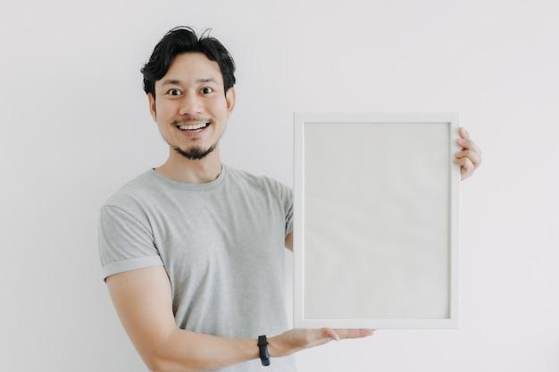 白い背景で隔離空のフォトフレームを保持している幸せな男