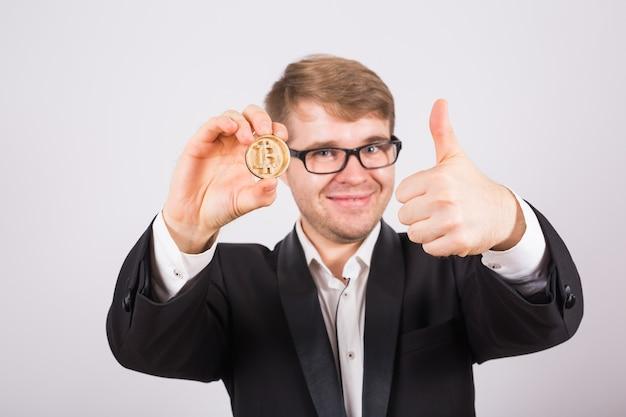 Счастливый человек держит большой биткойн и показывает палец вверх.