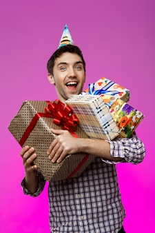 Happy man holding birthday gifts in boxes over purple wall.