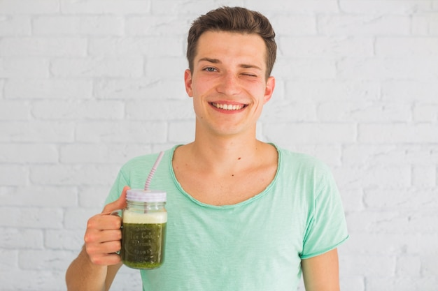 Happy man holding blended green smoothies in jar winking
