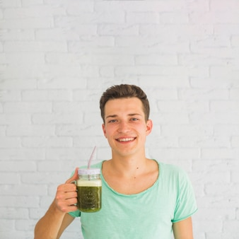 Happy man holding blended green smoothies in jar