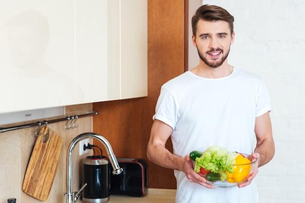 キッチンで野菜とボウルを保持し、正面を見て幸せな男