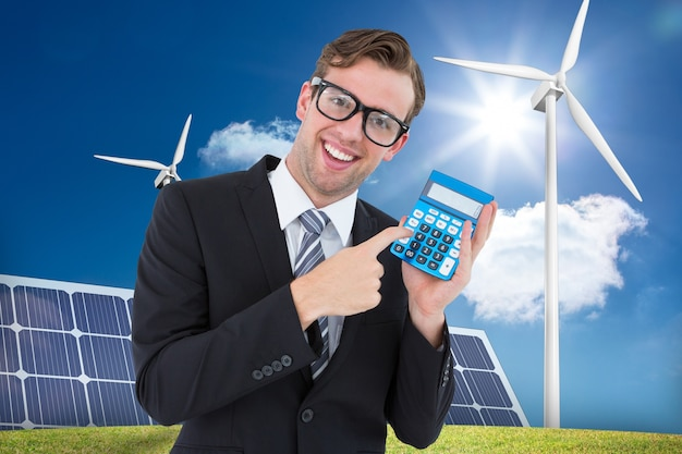 Happy man holding a calculator and a solar panel background