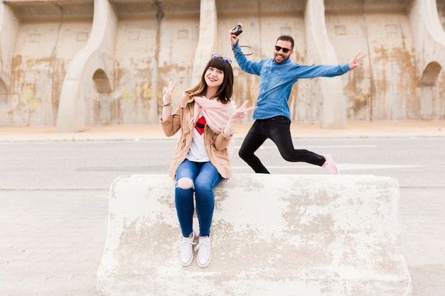 Happy man holding camera jumping in front of woman sitting over bench