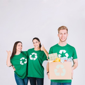 Happy man holding cardboard box with recycle items in front of women gesturing thumbs up