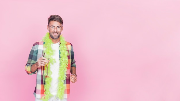 Happy man holding champagne flute with green boa around his neck standing against pink background