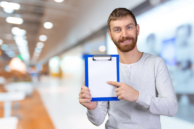 Happy man holding a clipboard and pointing with a finger