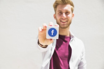 Happy man holding facebook icon cube