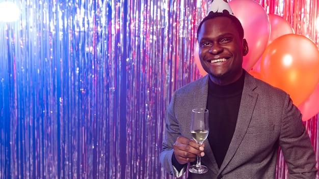 Uomo felice che tiene un bicchiere di champagne copia spazio