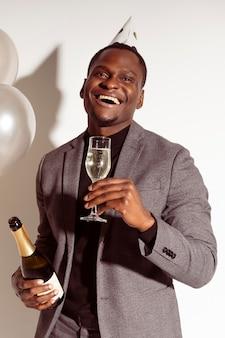 Uomo felice che tiene un bicchiere di champagne
